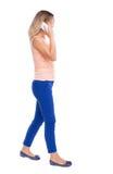 Vista laterale di una donna che cammina con un telefono cellulare ofgi posteriore di vista Immagini Stock Libere da Diritti