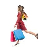 Vista laterale di una donna che salta con i sacchetti della spesa Fotografie Stock Libere da Diritti