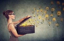 Vista laterale di una donna con la scatola piena delle idee brillanti che sono creative fotografia stock