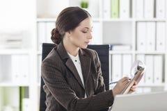 Vista laterale di una donna nel marrone con una lavagna per appunti Fotografia Stock Libera da Diritti