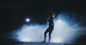 Vista laterale di una ginnasta femminile che fa verticale spaccato sul fascio di equilibrio contro il fondo nero archivi video