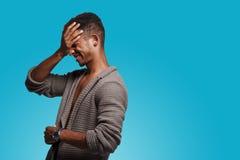 Vista laterale di una mano confusa della tenuta del giovane sul suo fronte, stante nel profilo, su un fondo blu fotografie stock