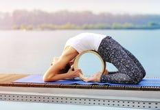 Vista laterale di una posa di pratica di yoga del piccione di ywoman Fotografia Stock