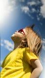 Vista laterale di una ragazza che guarda avanti nel parco, contro un fondo del cielo blu verticale Immagine Stock