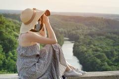 Vista laterale di una ragazza con una macchina fotografica Vista da una collina su una f verde Fotografia Stock