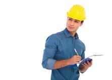 Vista laterale di una scrittura dello studente di ingegneria di costruzione sul clipb Fotografie Stock