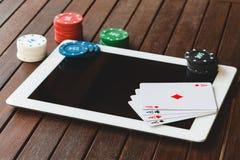 Vista laterale di una tavola verde della mazza con alcune carte della mazza su una tastiera Scommessa del concetto online immagini stock libere da diritti