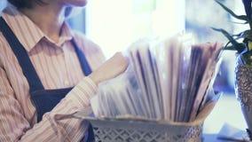 Vista laterale di una venditora che sceglie carta da imballaggio per un mazzo del fiore, colpo della pentola video d archivio