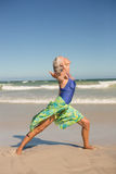 Vista laterale di yoga di pratica della donna mentre stando sulla riva Fotografia Stock