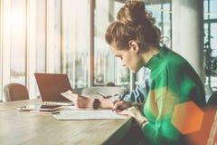 Vista laterale, giorno soleggiato, due giovani donne di affari che si siedono allo scrittorio in ufficio Prima donna per firmare  Immagine Stock
