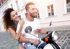Vista laterale integrale della guida felice delle coppie sulla motocicletta retro fotografie stock libere da diritti