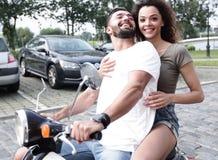 Vista laterale integrale della guida felice delle coppie sulla motocicletta retro fotografie stock