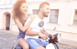 Vista laterale integrale della guida felice delle coppie sulla motocicletta retro fotografia stock libera da diritti