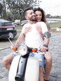 Vista laterale integrale della guida felice delle coppie sulla motocicletta retro immagini stock