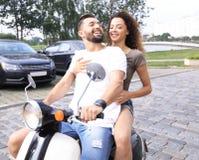 Vista laterale integrale della guida felice delle coppie sulla motocicletta retro immagine stock libera da diritti