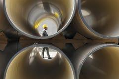 Vista laterale integrale di giovane architetto maschio che cammina dai tubi impilati al cantiere Fotografia Stock