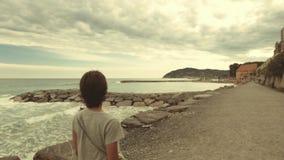 Vista laterale posteriore e della donna che cammina sul litorale e che esamina mare d'ondeggiamento Movimento lento, vecchio retr stock footage