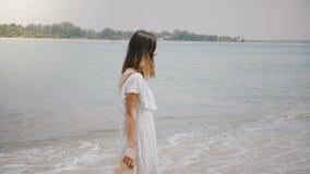 Vista laterale stupefacente sparata di giovane bella donna felice che cammina lungo la spiaggia tropicale idilliaca dell'oceano c video d archivio