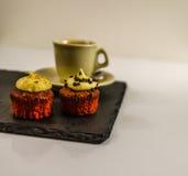 Vista laterale su due bigné dolci, sulla fragola e sul cioccolato cremoso fotografia stock libera da diritti