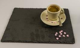 Vista laterale su piccolo caffè nero in una tazza, porpora dolce rovesciata h Fotografia Stock