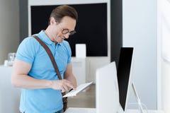 Vista laterale sull'uomo dell'affare che prova la tastiera del modello Fotografie Stock