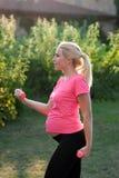 Vista laterale sulla donna incinta con le teste di legno Fotografia Stock Libera da Diritti