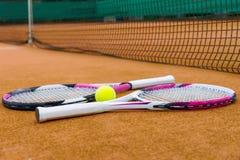 Vista laterale sulle racchette di tennis con una pallina da tennis sul campo in argilla Fotografia Stock