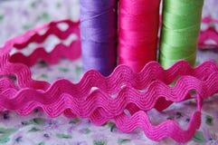 Vista laterale vicina delle bobine variopinte del filo in porpora, in rosa ed in verde immagini stock libere da diritti