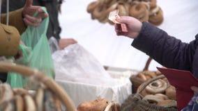 Vista los rollos de pan de forma anular de compra sazonados con las semillas de amapola en un precio de la ciudad Mano que paga e almacen de metraje de vídeo