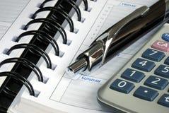 Vista macra de la calculadora, de la pluma, y del diario Foto de archivo libre de regalías