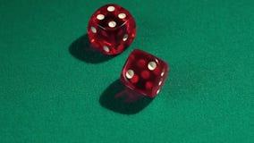 Vista macra de los dados rojos que caen en la tabla verde, jugando al juego en el casino de Vegas almacen de metraje de vídeo