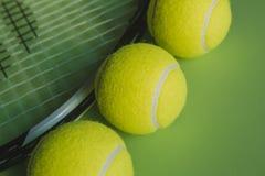 Vista macra de tres pelotas de tenis y de una estafa de tenis en fondo verde Fotografía de archivo