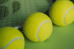 Vista macra de tres pelotas de tenis y de una estafa de tenis en fondo verde Fotografía de archivo libre de regalías