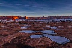 Vista magnífica de charcos congelados en el piso de la piedra arenisca del parque nacional de los arcos y de montañas que brillan Fotografía de archivo
