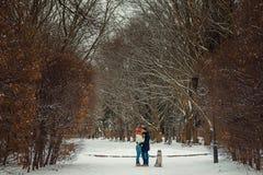 Vista magnífica de los pares que se besan alegres que pasan tiempo con el husky siberiano en el parque del invierno Fotos de archivo