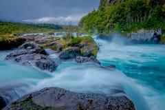 Vista magnífica del agua que pasa a través de la roca volcánica que crea las cascadas, formada por una erupción del volcán Osorno fotografía de archivo