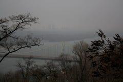 Vista melancólica do monte do parque na ponte do rio com silhuetas das construções fotos de stock
