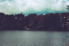 Vista misteriosa sopra un lago ad una casa nascosta immagini stock