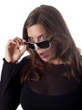 Vista moreno bonita sobre seus óculos de sol chocados Imagem de Stock Royalty Free