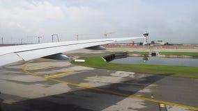 Vista na asa do avião e no aeroporto, guindastes de torre na skyline video estoque