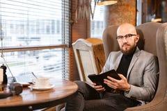 Vista na câmera Homem novo com a barba, vestindo um terno nos vidros bebendo o café de um copo successful imagem de stock