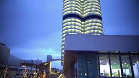 Vista na construção iluminada alta do negócio, arquitetura moderna, árvores decoradas filme