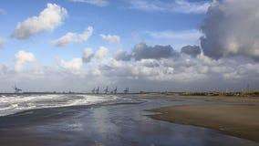 Vista na costa belga com os guindastes do porto do zeebrugge no fundo fotos de stock