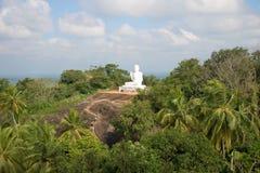 Vista na escultura branca de uma Buda de assento na montanha Ambasthala Fotos de Stock Royalty Free