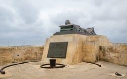 Vista na escultura recostado no próximo do memorial de guerra de Bell do cerco com um sinal da descrição em Malta da parte inferi fotos de stock royalty free
