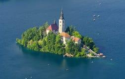 A vista na ilha com a igreja no lago sangrou, Eslovênia Fotos de Stock Royalty Free
