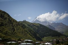 A vista na parte superior da montanha à cidade de Geórgia na luz solar brilhante imagem de stock