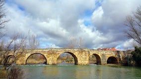 Vista na ponte antiga de pedra sobre o CEA do rio à proximidade da cidade Sahagun, Espanha Rio silencioso, dia ensolarado, SK neb Imagens de Stock Royalty Free