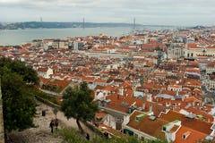 Vista nad Lisbon Baixa terenem Tagus rzeką Cristo Reja statuą i 25, De Abril Przerzucający most Zdjęcia Royalty Free