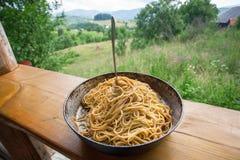 Vista naturale e pentola con pasta italiana con il pomodoro e la forcella Alimento degli spaghetti sul terrazzo della casa rurale Immagini Stock Libere da Diritti